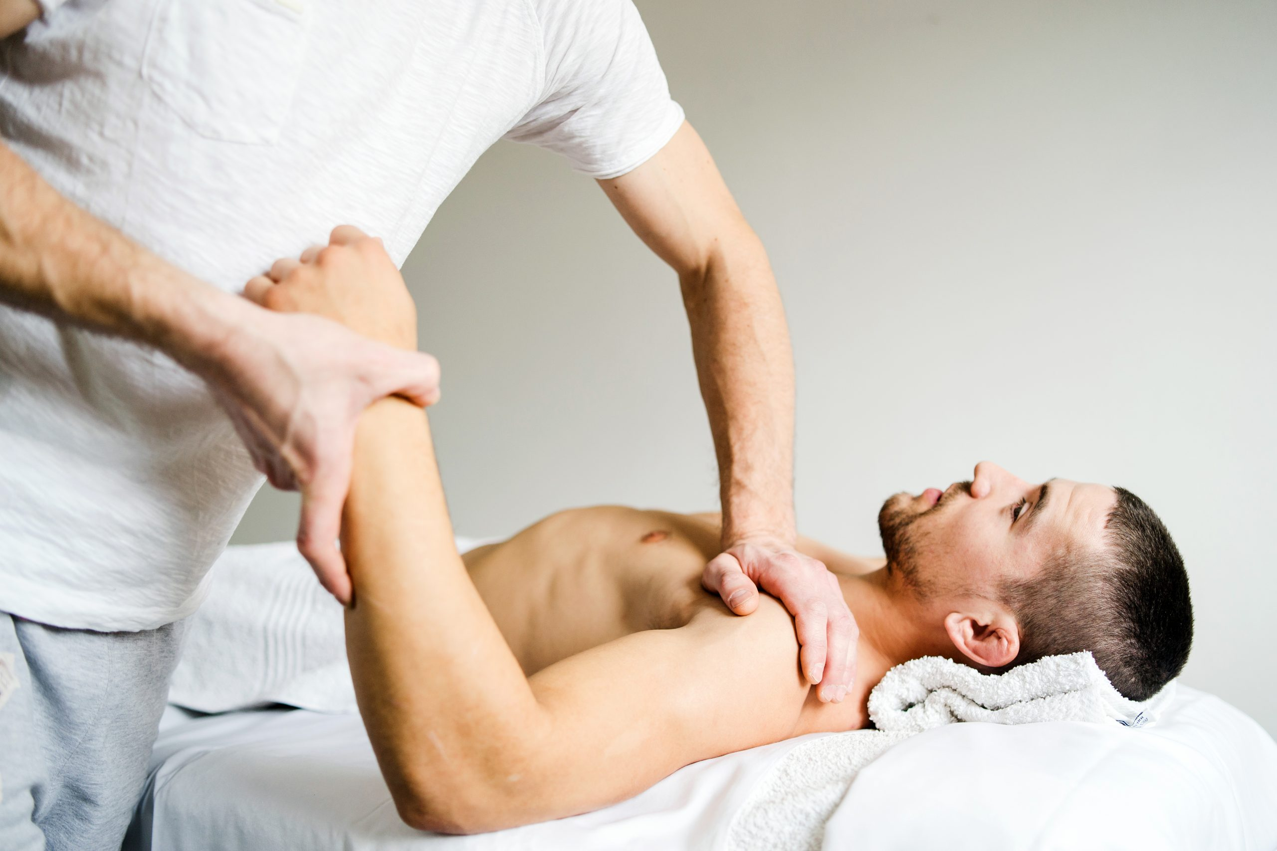 Male physio therapist giving sport massage to the young Man at the salon