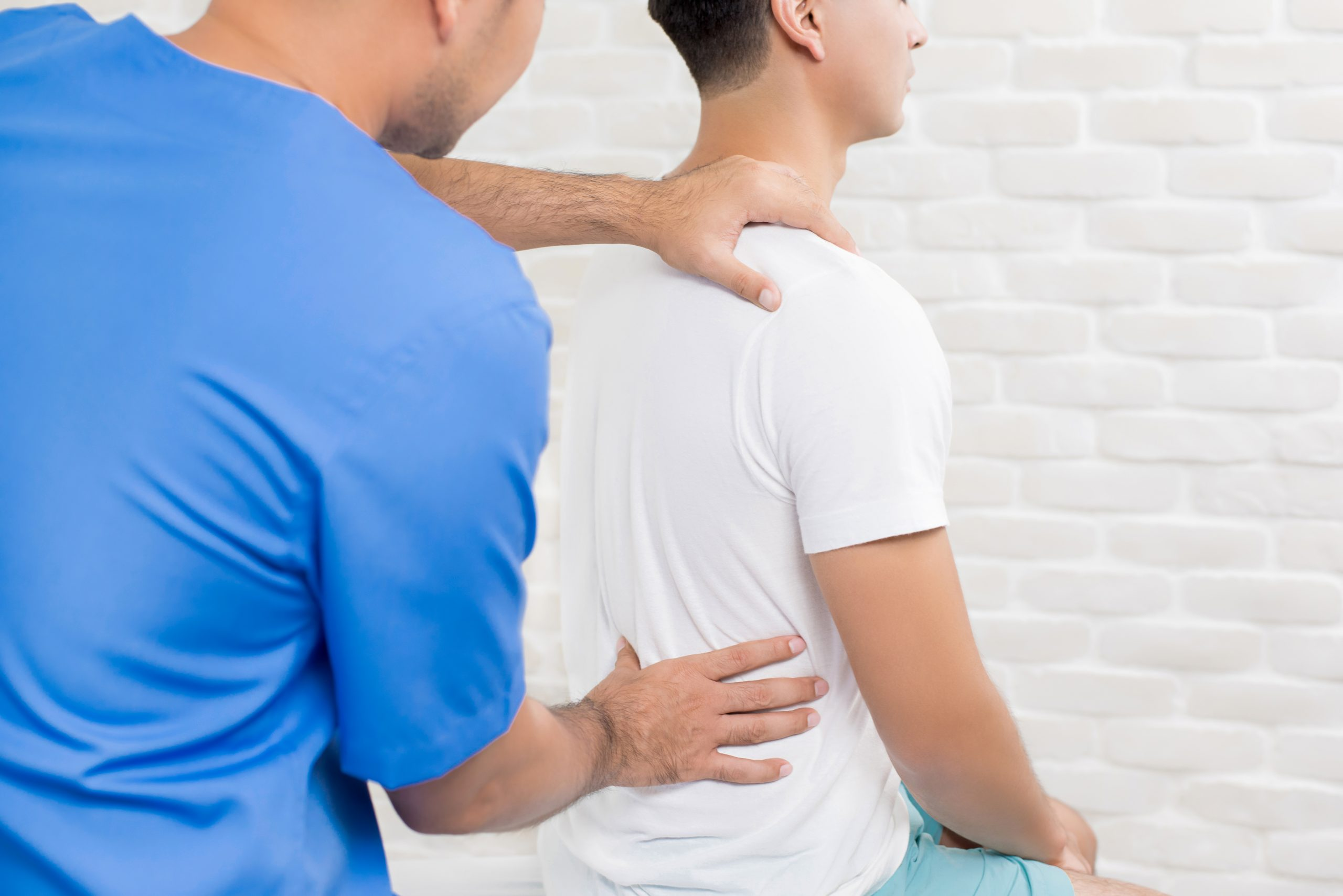 Male doctor therapist treating lower back pain patient in clinic or hospital